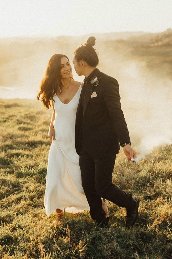 Brunette bride wearing Grace Loves Lace Arlo Gown walking with groom in smokey field