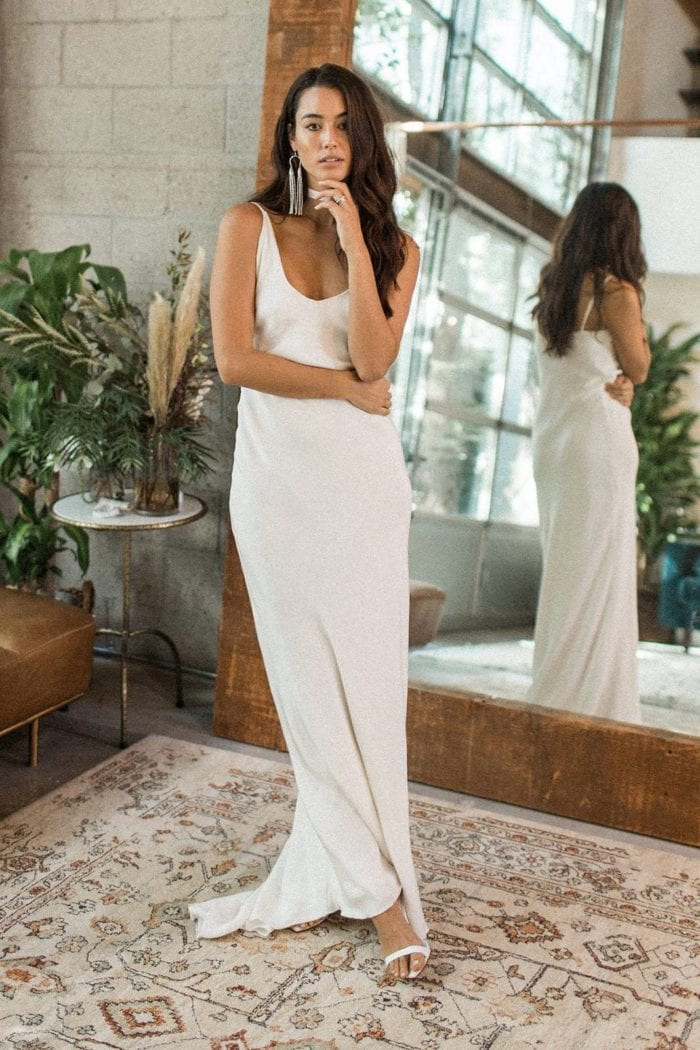 Brunette bride wearing Grace Loves Lace Arlo Gown in front of mirror