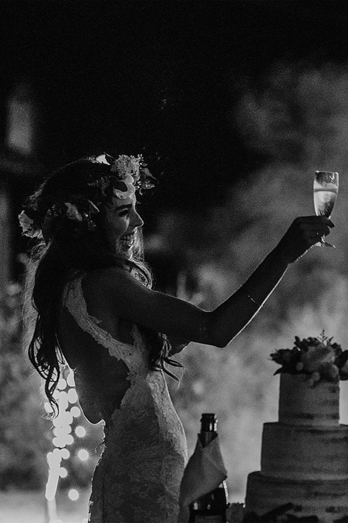 Black and white shot of bride wearing Grace Loves Lace Alexandra Gown raising champagne glass in air