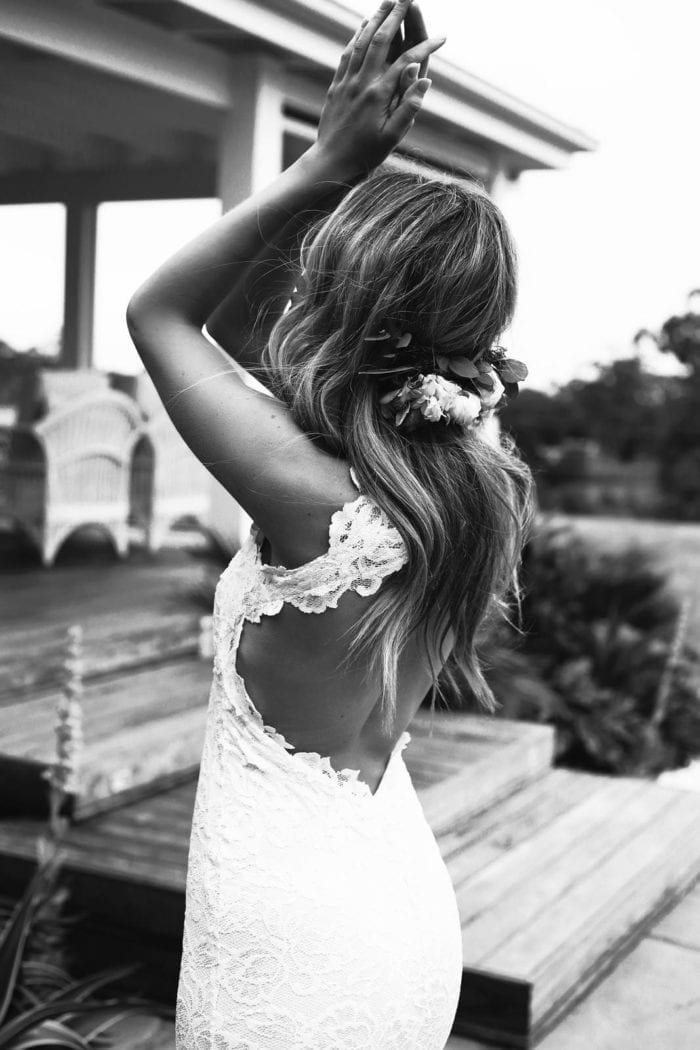 Black and white shot of bride wearing Grace Loves Lace Alexandra Gown with hands in air