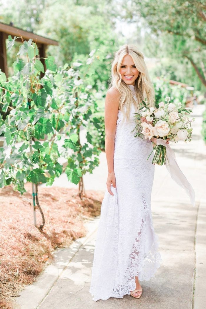Bride wearing Grace Loves Lace Alexandra Gown holding bouquet and train