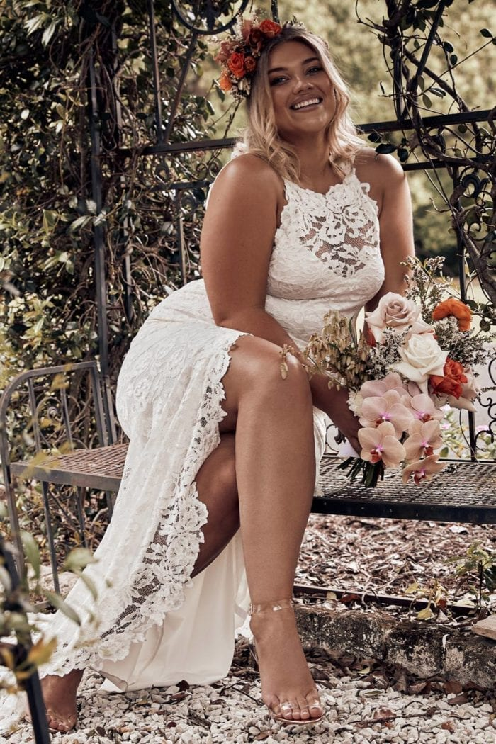 Bride wearing Grace Loves Lace Alexandra Gown sitting down holding bouquet