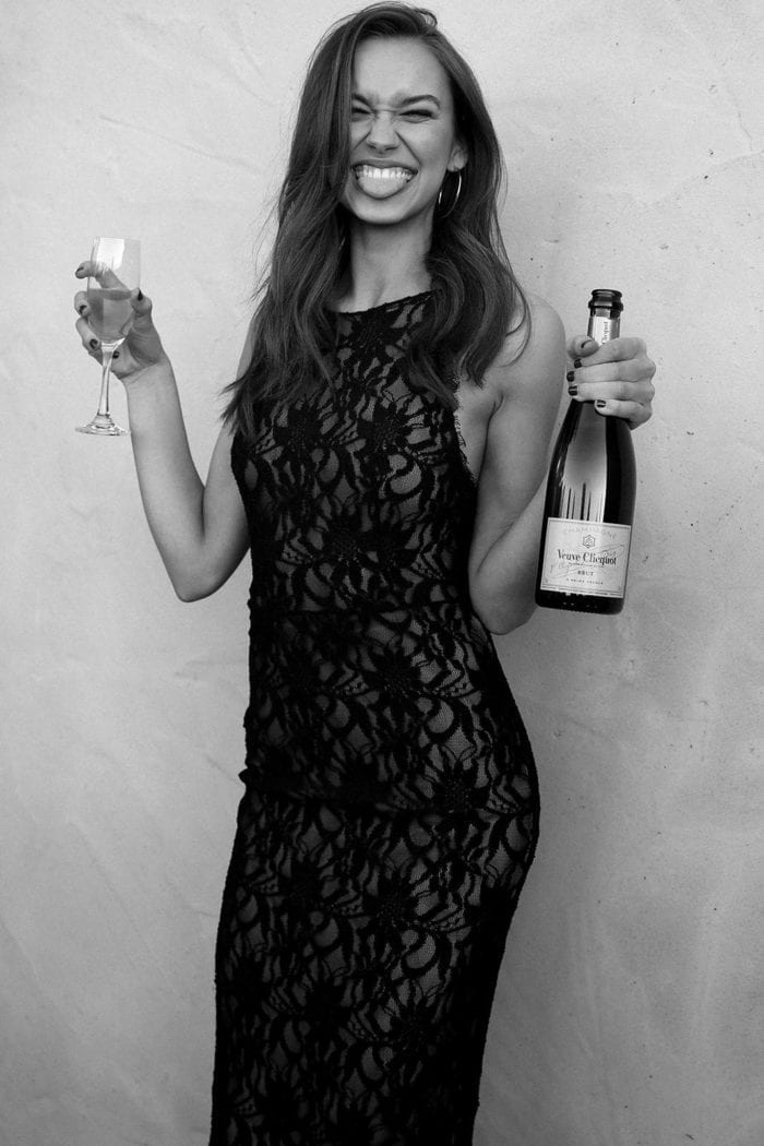Black and white shot of bridesmaid wearing Grace Loves Lace Cruz Dress holding champagne glass and bottle while poking tongue out