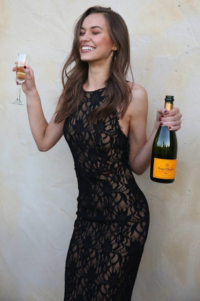 Bridesmaid wearing Grace Loves Lace Cruz Dress holding champagne glass and bottle while poking tongue out