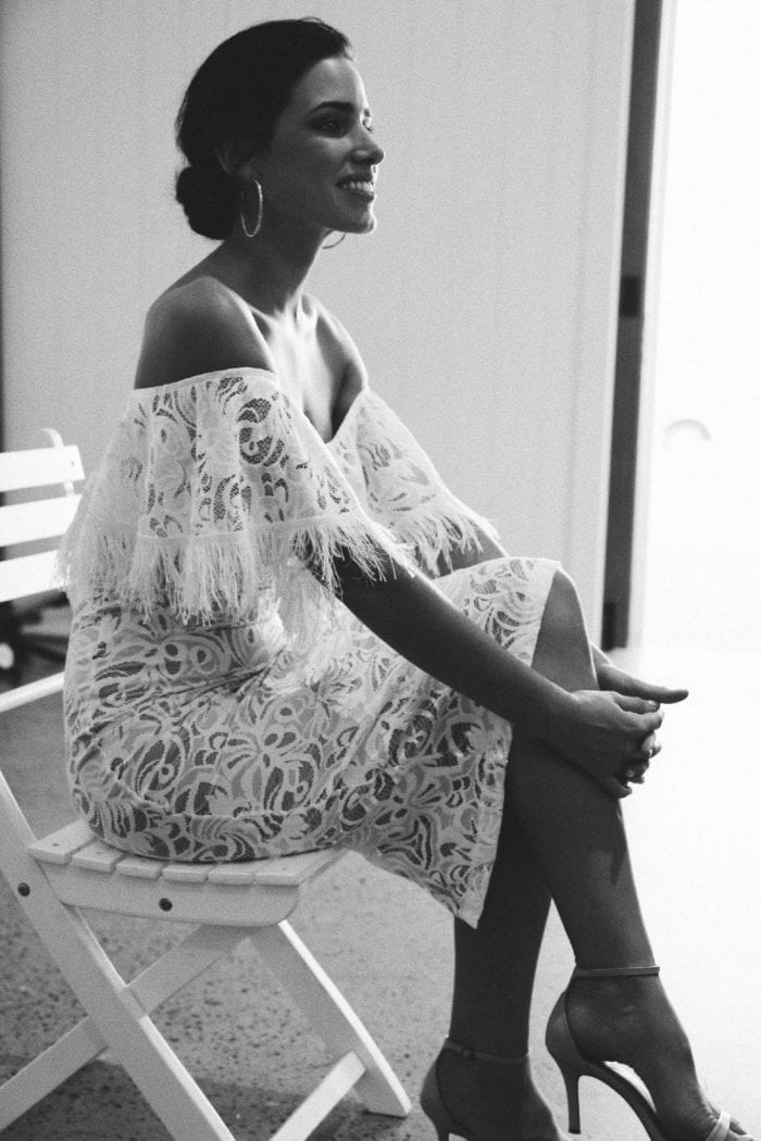 Black and white shot of bridesmaid wearing Grace Loves Lace Dominga Dress with Nude Lining with statement earrings sitting down