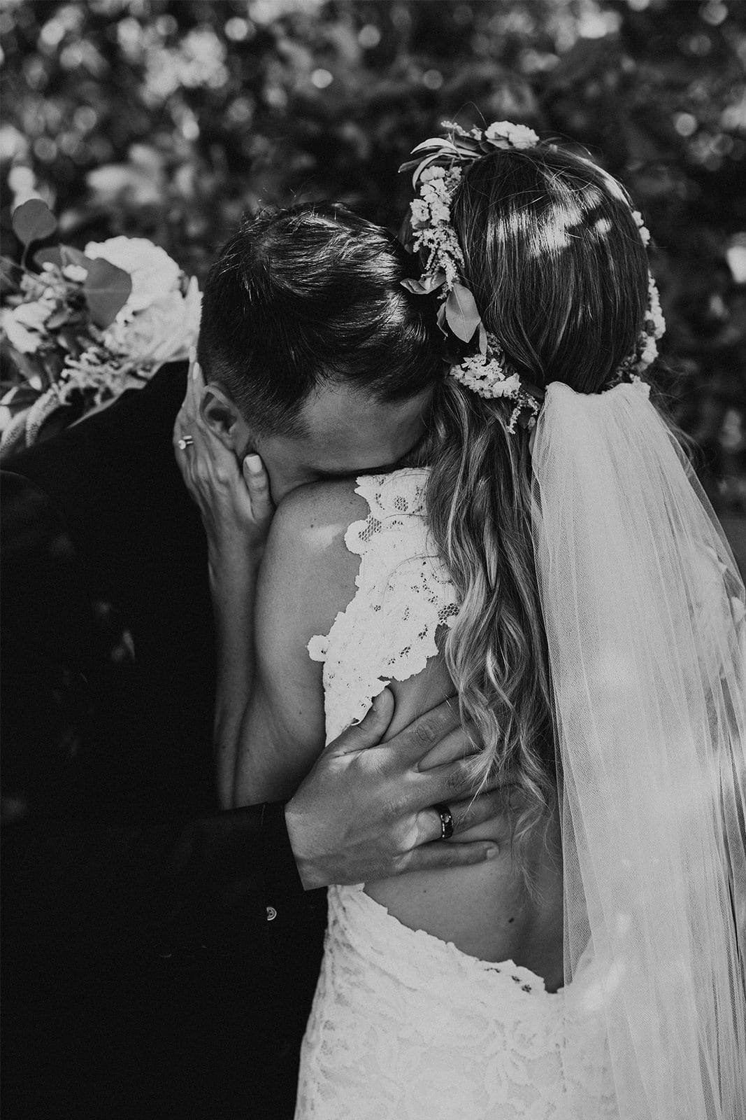 Black and white shot of bride wearing Grace Loves Lace Alexandra Gown with groom leaning on shoulder
