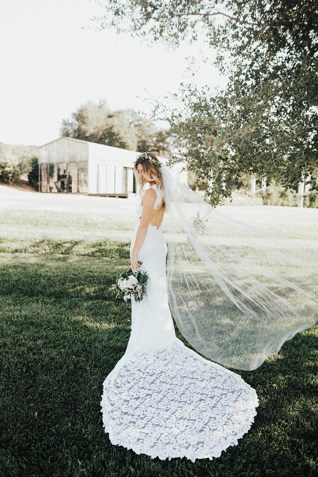 Back shot of bride wearing Grace Loves Lace Alexandra Gown holding bouquet