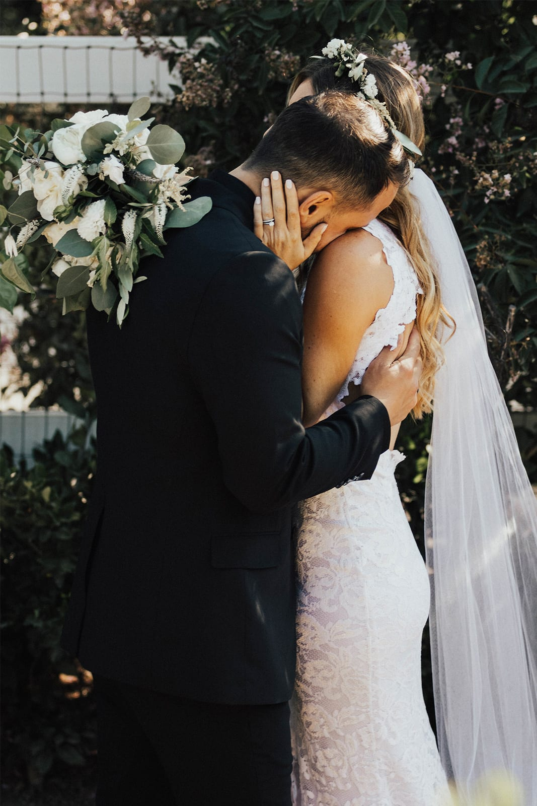 Bride wearing Grace Loves Lace Alexandra Gown with groom leaning on shoulder
