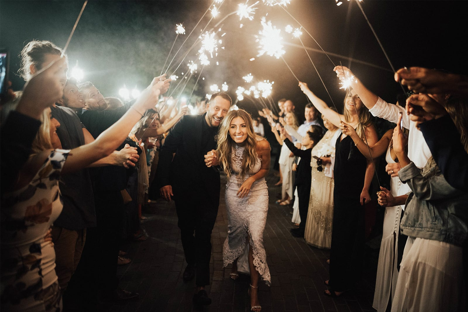Bride wearing Grace Loves Lace Alexandra Gown holding hands with groom under archway made of sparklers