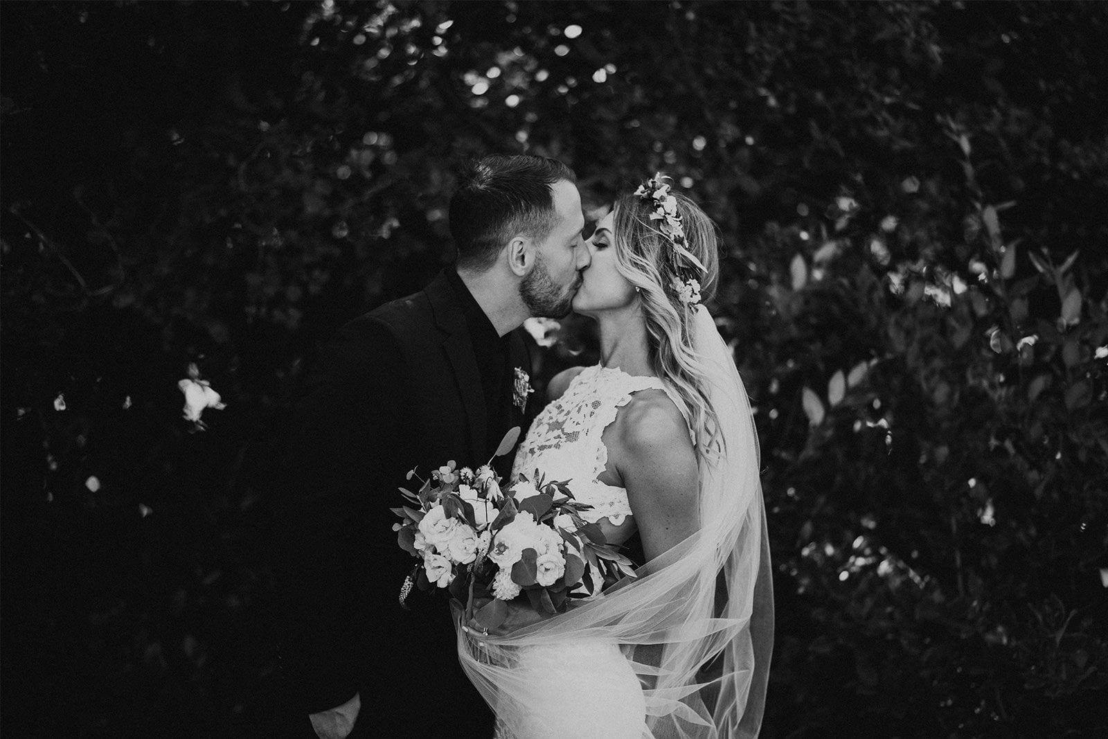 Black and white shot of bride wearing Grace Loves Lace Alexandra Gown kissing groom