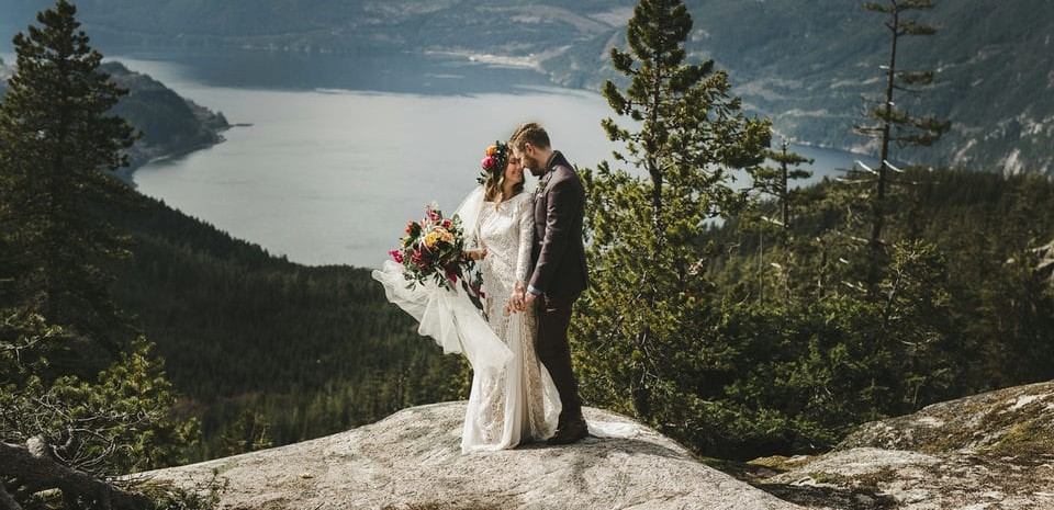 Bride wearing Grace Loves Lace Inca Gown holding hands with groom