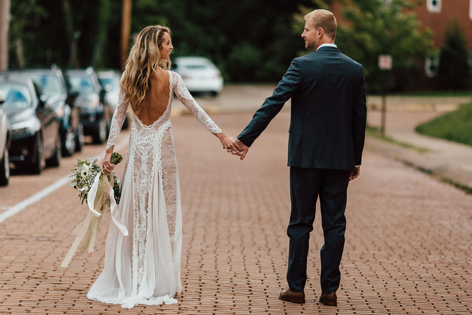 Bride wearing Grace Loves Lace Inca Gown holding hands with groom holding bouquet