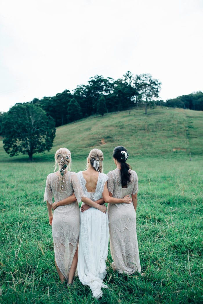 Back shot of bridesmaids wearing Grace Loves Lace Lace Maxi Dress in Champagne standing with bride interlocking arms