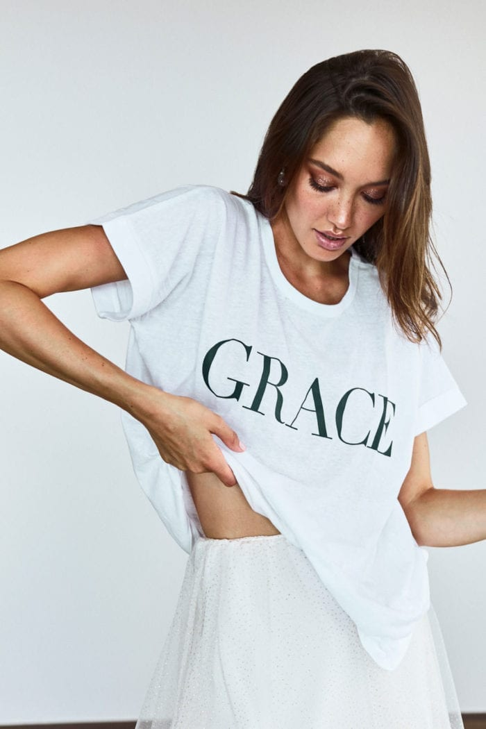 Bridesmaid wearing Grace Loves Lace Grace Tee in White holding shirt in hand