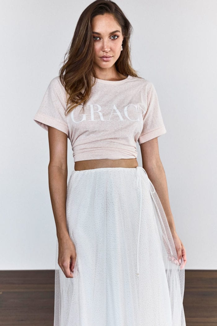 Bridesmaid wearing Grace Loves Lace Grace Tee in Blush holding skirt in hand