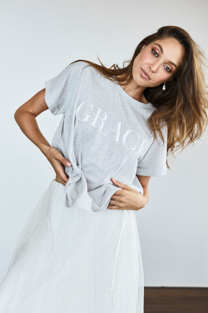 Bridesmaid wearing Grace Loves Lace Grace Tee in Grey holding shirt in hands