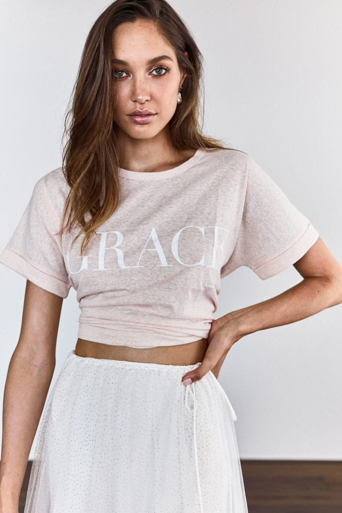 Bridesmaid wearing Grace Loves Lace Grace Tee in Blush with hand on hip
