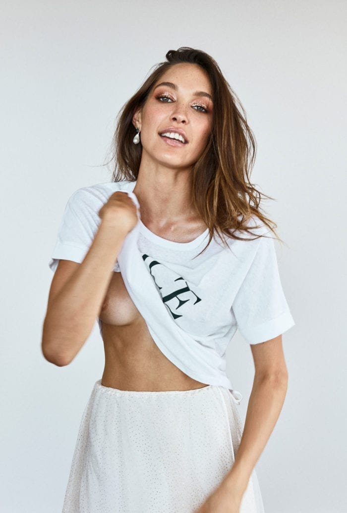 Bridesmaid wearing Grace Loves Lace Grace Tee in White holding shirt in hand revealing breast