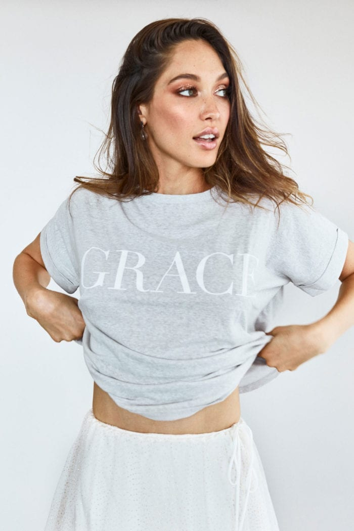 Bridesmaid wearing Grace Loves Lace Grace Tee in Grey holding shirt in hands showing midriff