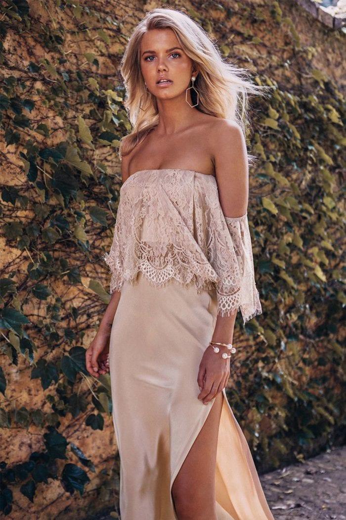 Bridesmaid wearing Grace Loves Lace Belle Silk Split Skirt in Sandstone with statement earrings
