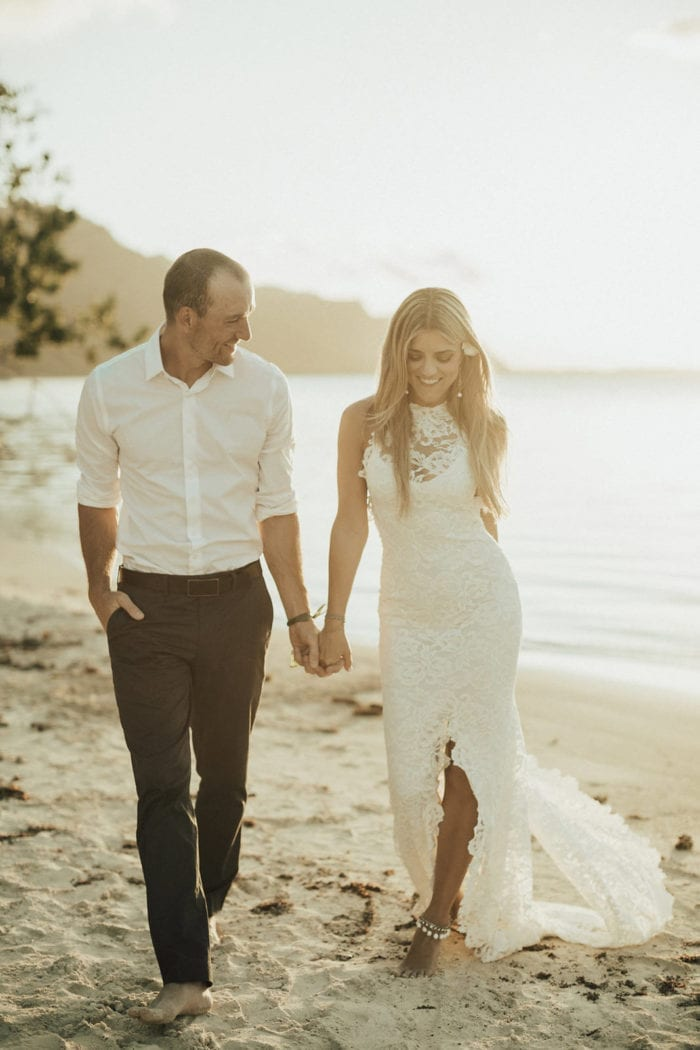 Bride wearing Grace Loves Lace Hera Anklets walking on beach holding hands with groom