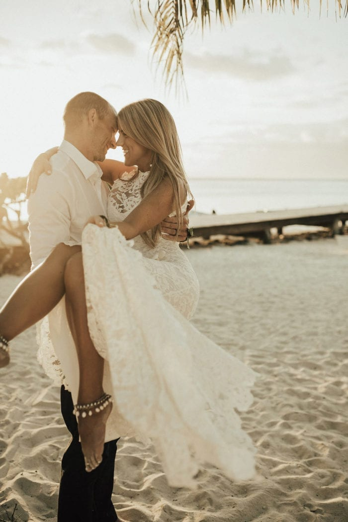 Bride wearing Grace Loves Lace Hera Anklets on beach being held by groom