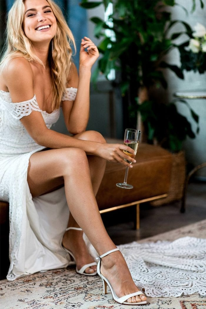 Bride wearing Grace Loves Lace Dosa Heels in White holding champagne glass sitting on brown leather sofa