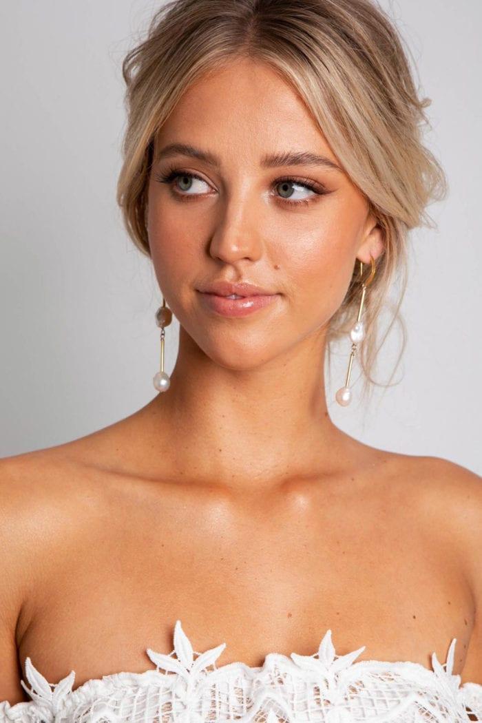 Bride wearing Grace Loves Lace Sundance Earrings in Gold looking to the side