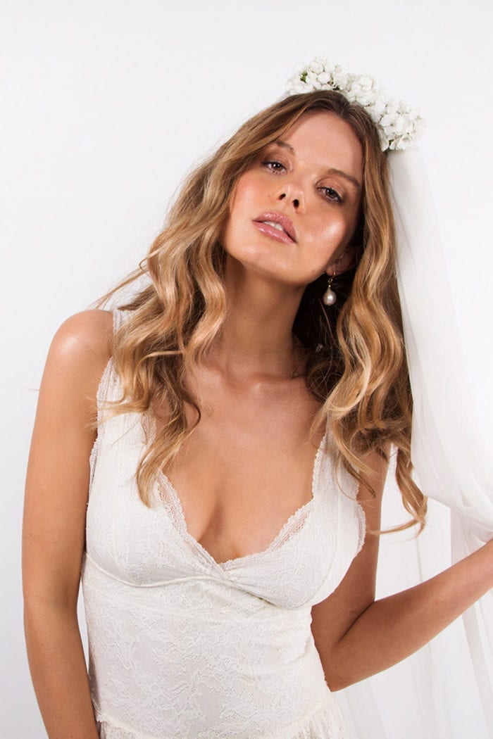 Bride wearing Grace Loves Lace Maya Earrings holding veil in hand