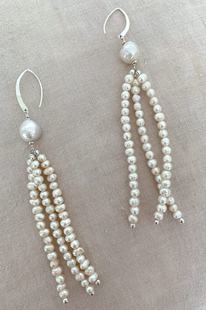 Grace Loves Lace Mata Earrings laying on cream linen