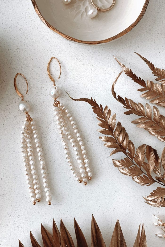 Grace Loves Lace Mata Earrings laying on white table surrounded by rose gold items