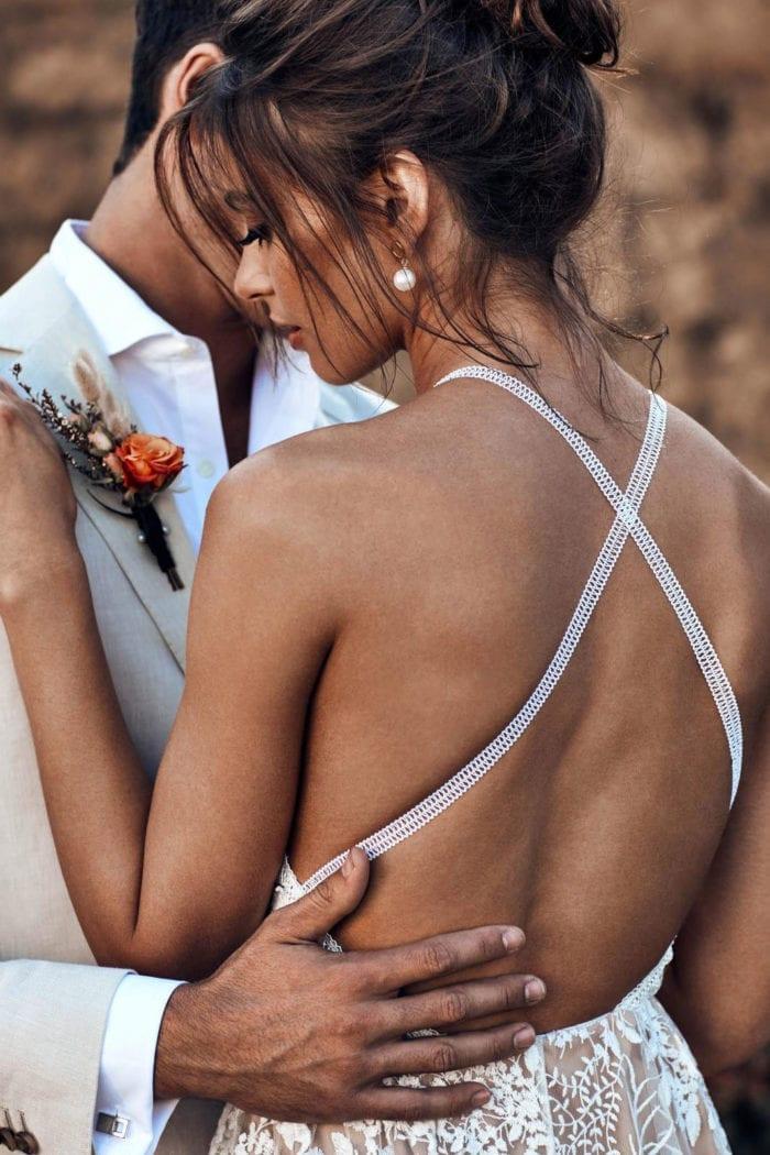Back shot of bride wearing Grace Loves Lace Lyra Earrings being held by groom