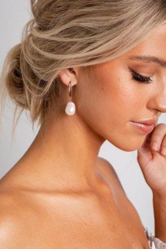 Bride wearing Grace Loves Lace Gaia Earrings looking down