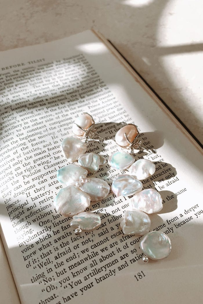 Grace Loves Lace Essie Earrings laying on open book