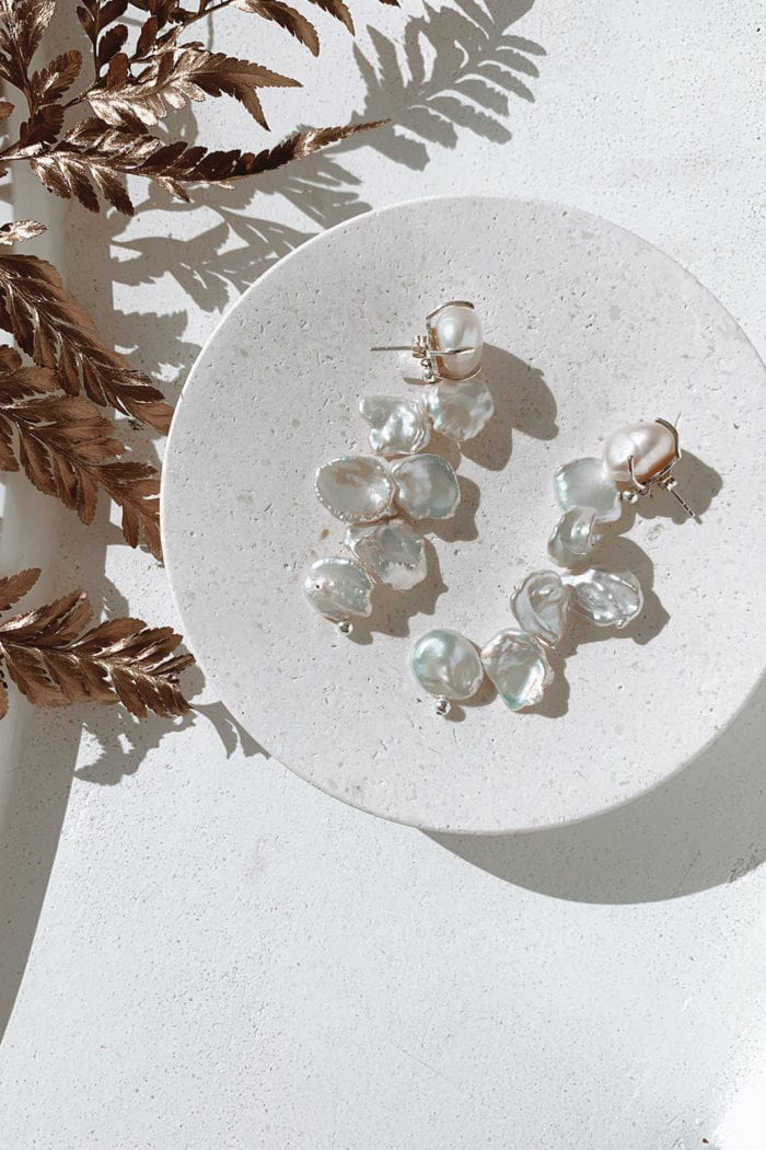 Grace Loves Lace Essie Earrings laying on white stone circle