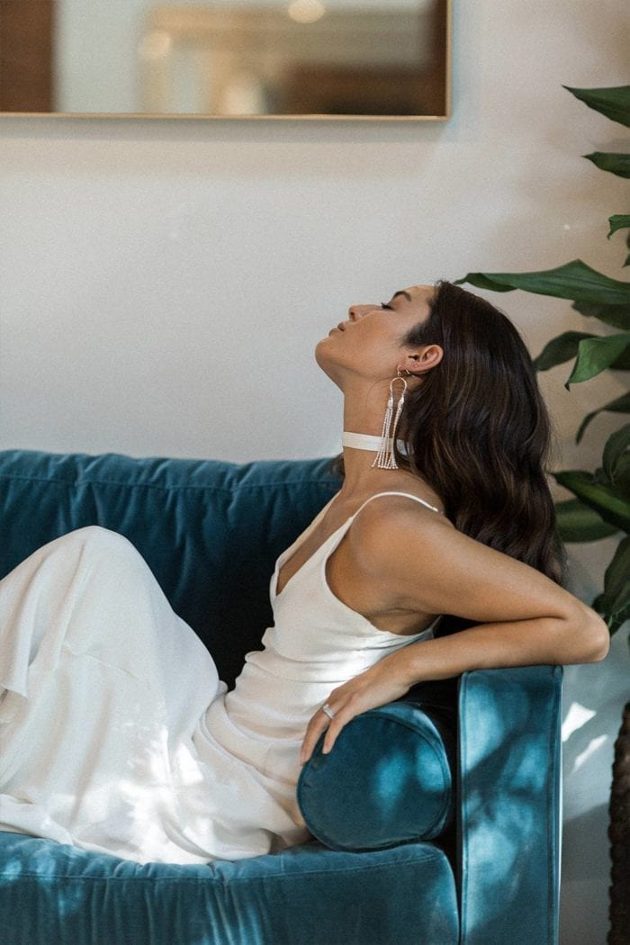 Bride wearing Grace Loves Lace Chase Silk Choker laying on turquoise sofa