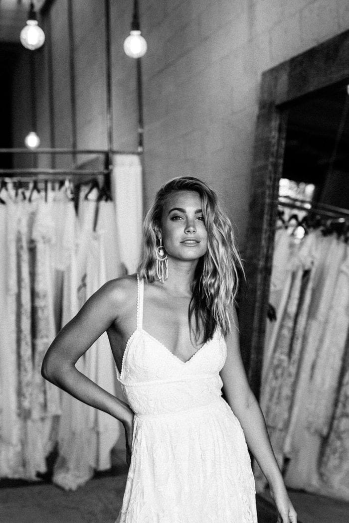 Black and white shot of bride wearing Grace Loves Lace Amilla Earrings in White Pearl and Gold with hand on hip