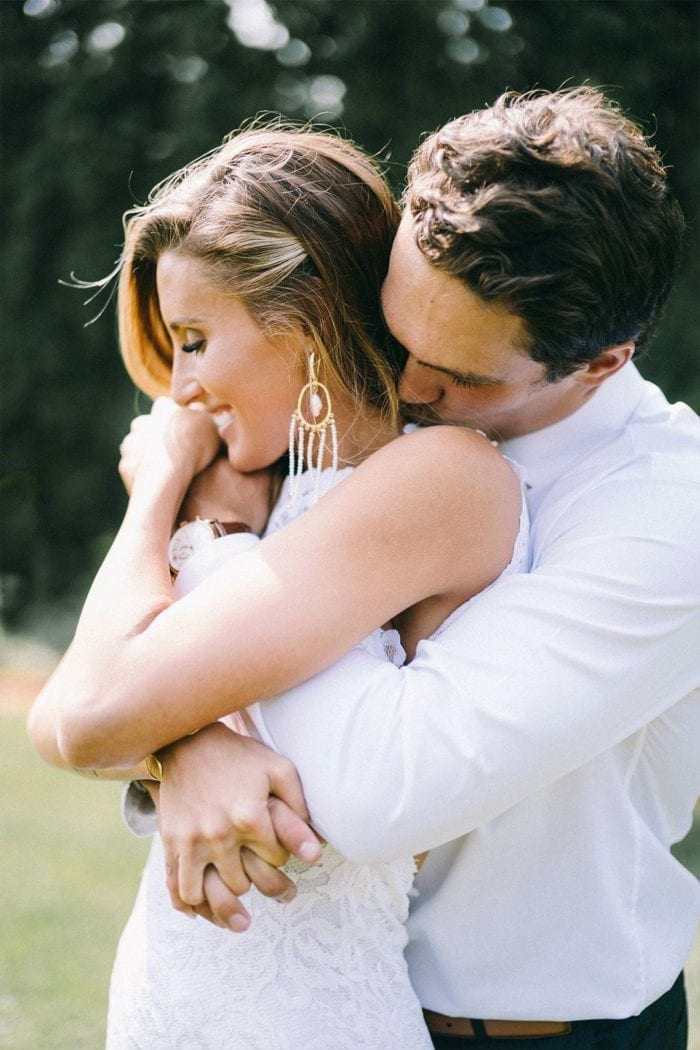 Bride wearing Grace Loves Lace Amilla Earrings in White Pearl and Gold being held by groom