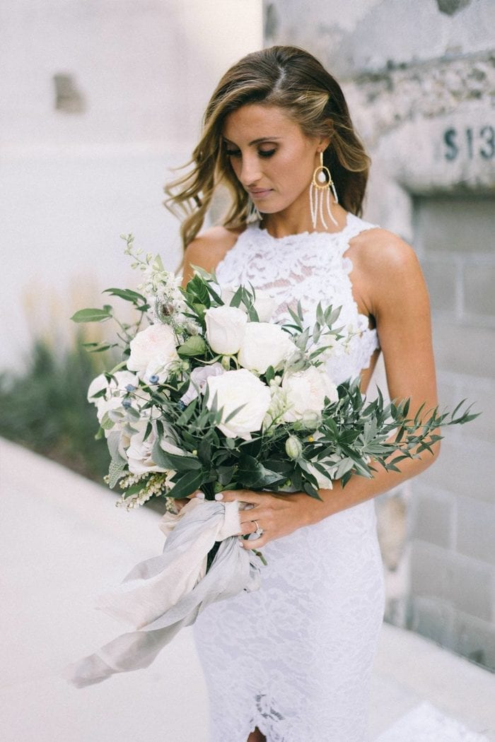 Bride wearing Grace Loves Lace Amilla Earrings in White Pearl and Gold holding bouquet