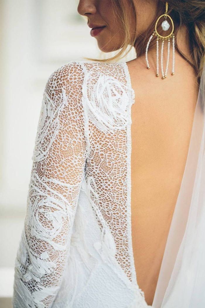 Close-up of bride wearing Grace Loves Lace Amilla Earrings in White Pearl and Gold