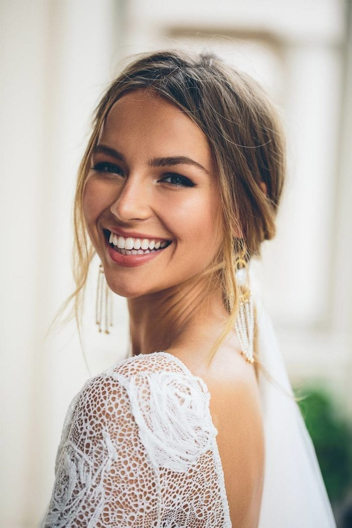 Bride wearing Grace Loves Lace Amilla Earrings in White Pearl and Gold looking over shoulder
