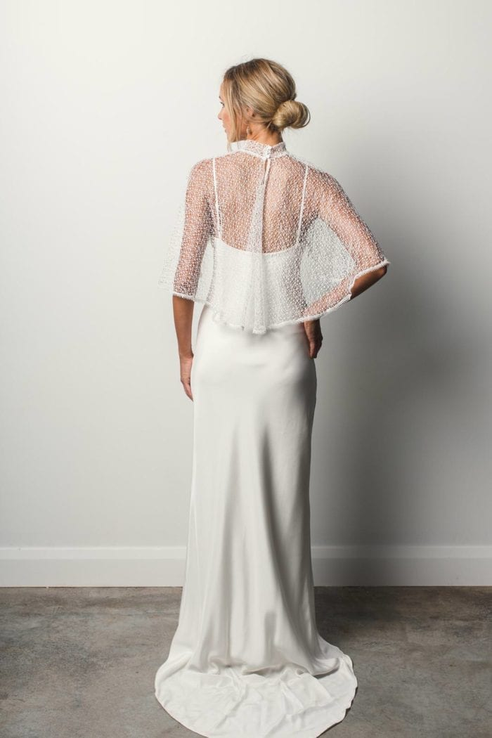Back shot of bride wearing Grace Loves Lace Yoko Cape with hand on hip