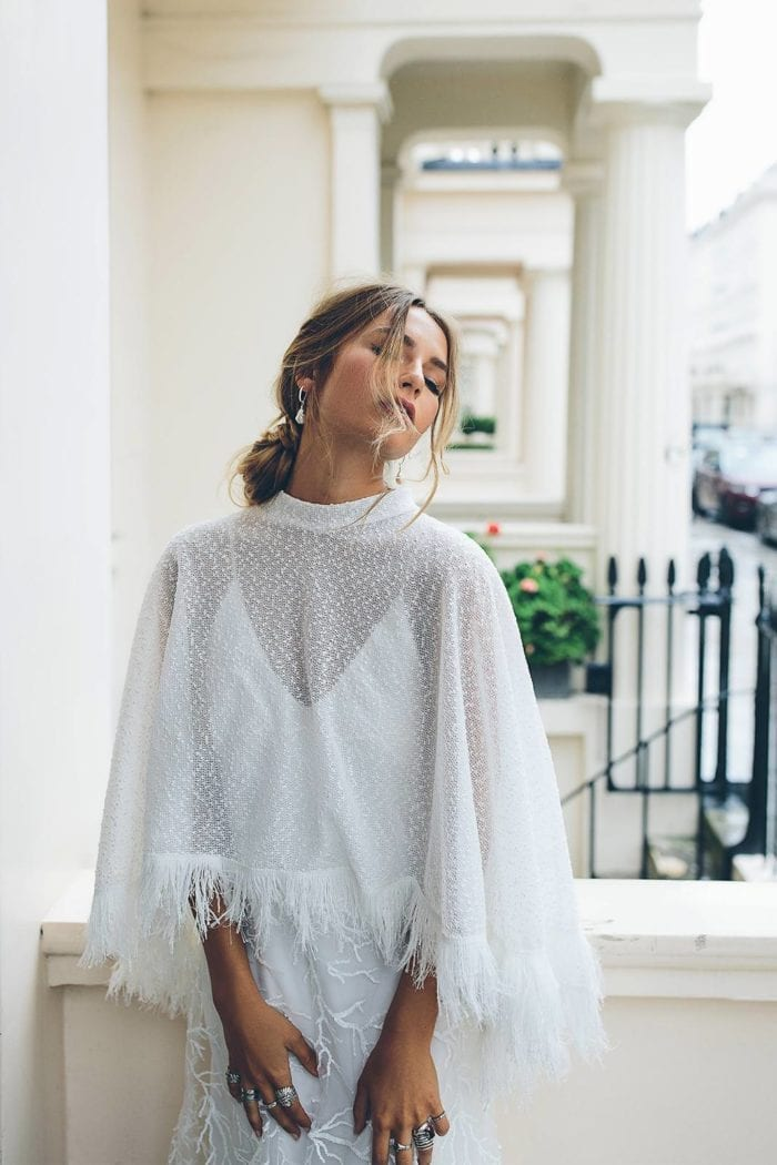 Bride wearing Grace Loves Lace Pierre Cape leaning against wall