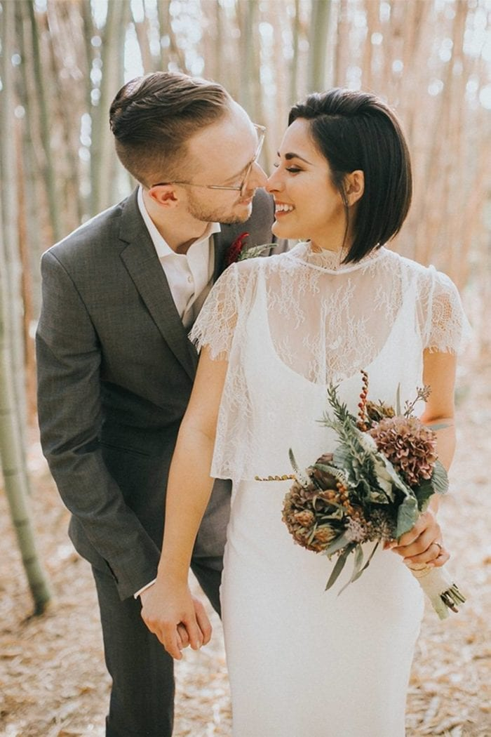 Bride wearing Grace Loves Lace Mason Top holding bouquet standing with groom