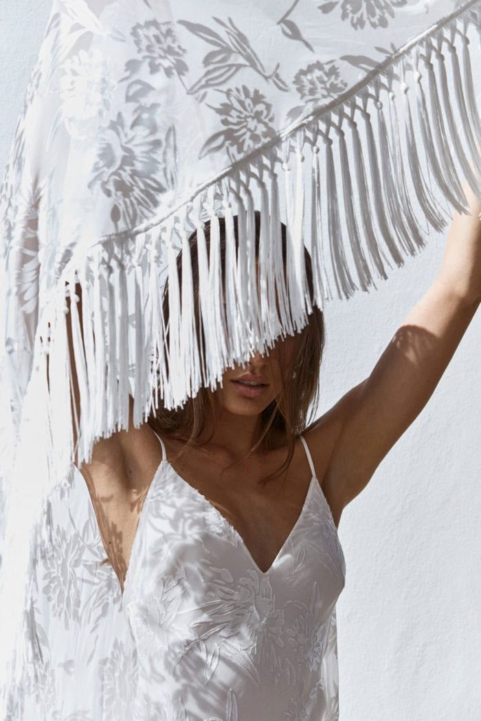Close-up of bridesmaid holding Grace Loves Lace Loyola Shawl above her head casting shadows on her torso