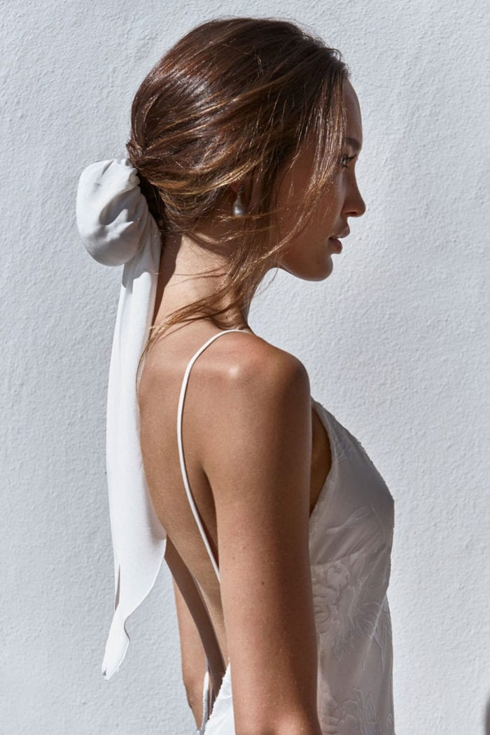 Side shot of bride wearing Grace Loves Lace Silk Hair Bun and pearl earrings