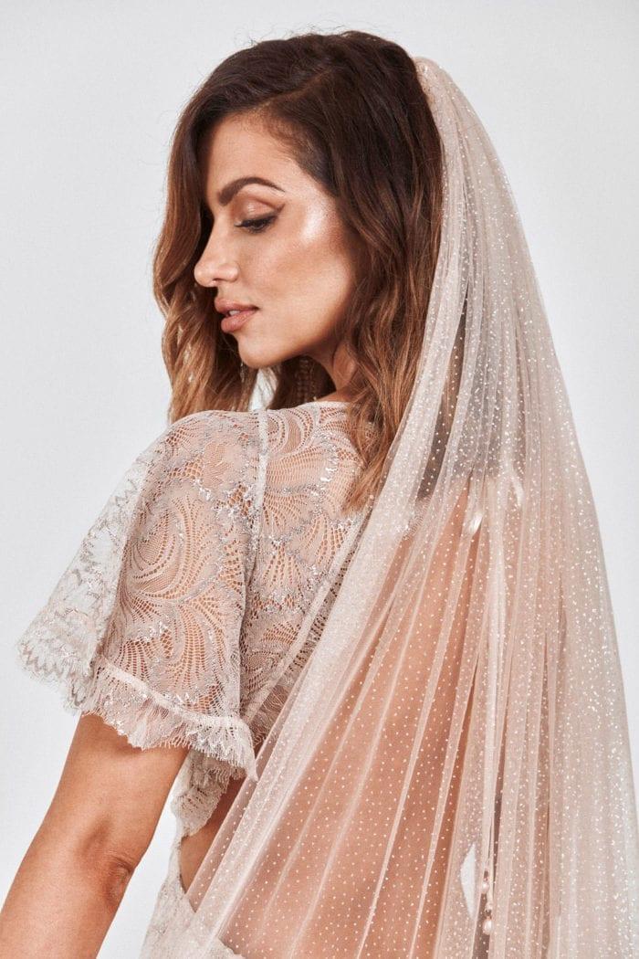 Back shot of bride wearing Grace Loves Lace Shimmy Veil in Nude Silver looking downward over her shoulder