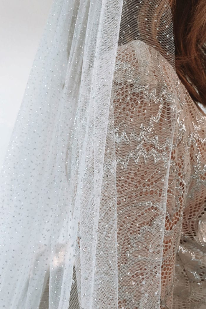 Close-up shot of bride wearing Grace Loves Lace Shimmy Veil in Ivory Silver