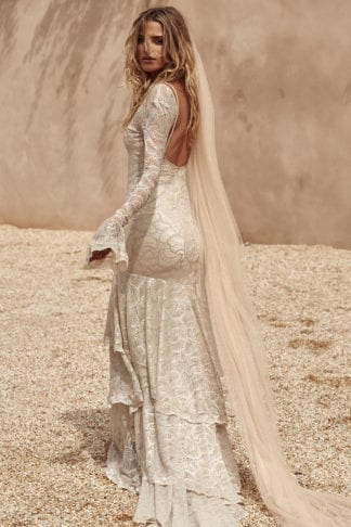Back shot of bride wearing Grace Loves Lace Shimmy Veil in Nude Gold looking over shoulder on a beach