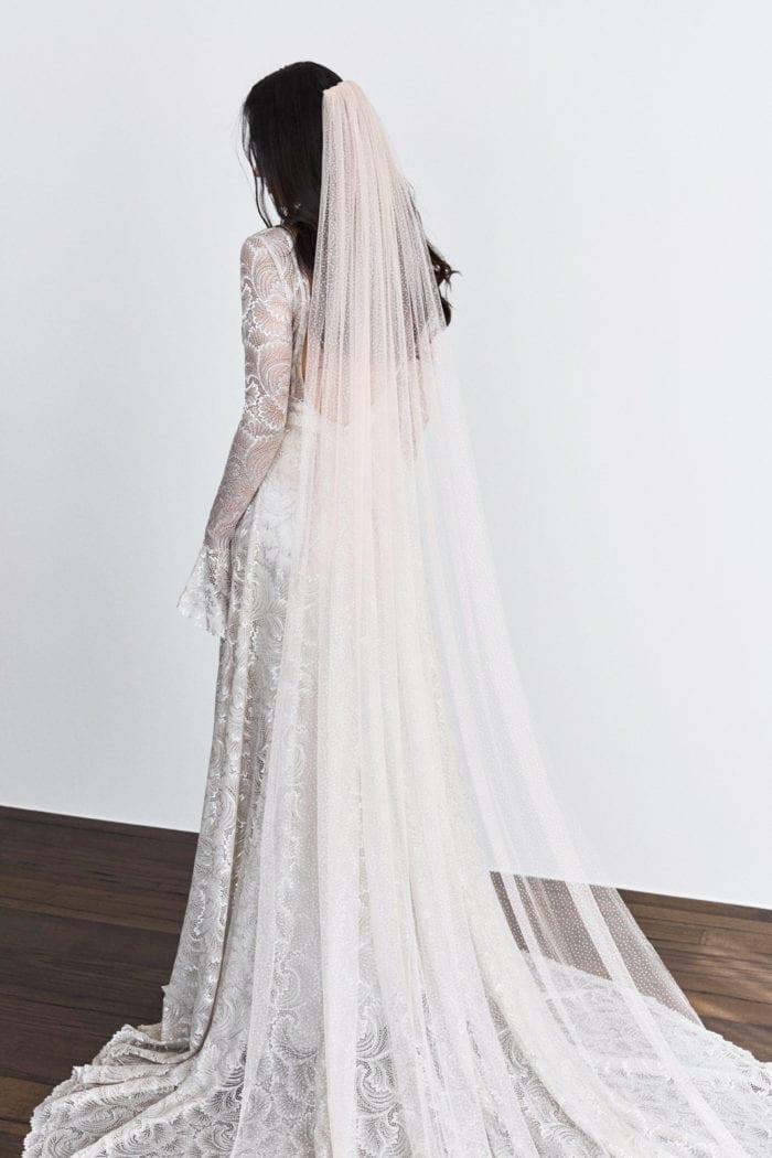 Back shot of bride wearing Grace Loves Lace Shimmy Veil in Ivory Silver